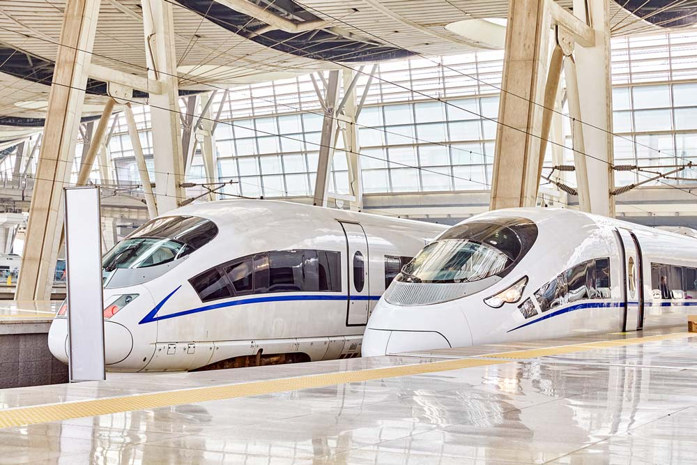 Mega Projects | Two high speed trains waiting in a station.